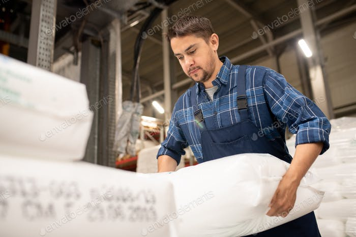 Young worker of polymer production factory loading sacks with plastic granules