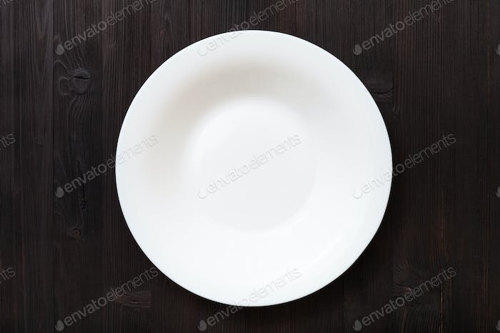 top view of white deep plate on dark brown table