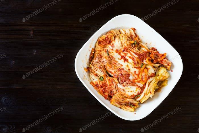 Draufsicht von Kimchi in Schüssel auf dunklem Holztisch