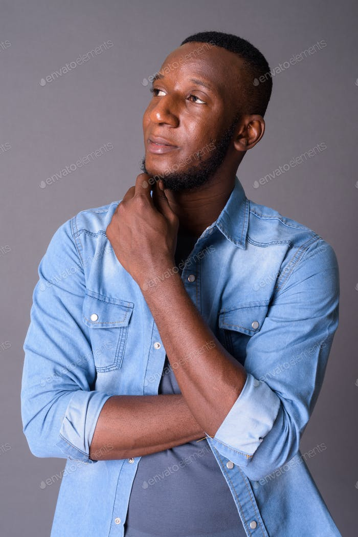 Young handsome African man with short hair against gray backgrou