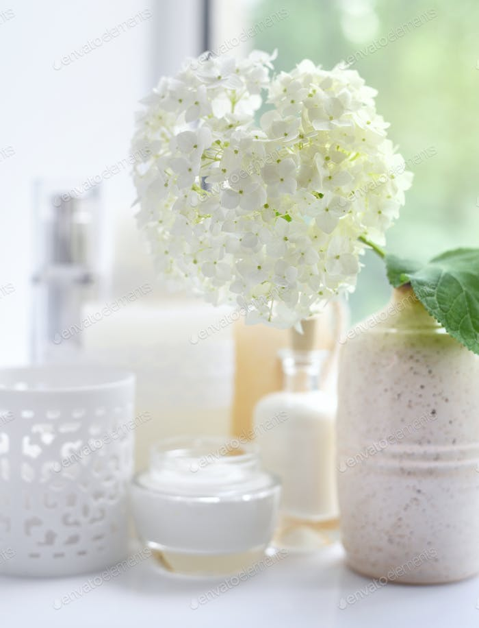 White hydrangea with spa products on a white background