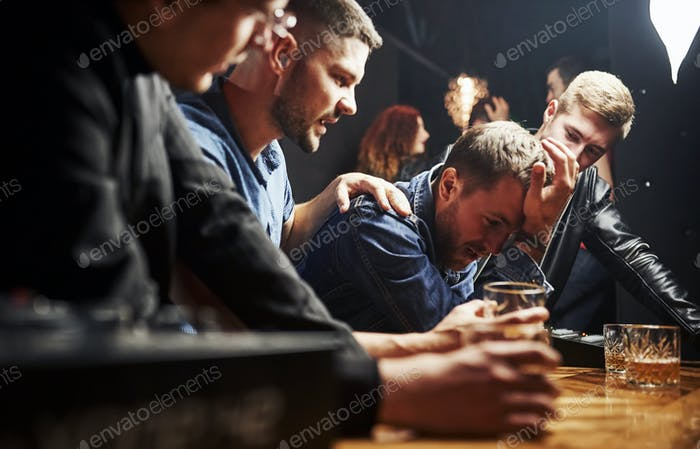Guy feels awful. Friends resting in the pub with alcohol in hands. Having conversation