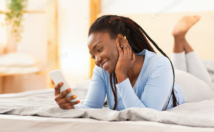 Cheerful Afro Woman Using Smartphone Lying In Bed