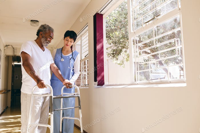 Female nurse helping senior male patient to walk with walker in corridor at retirement home