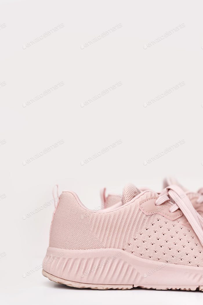Pink female sneakers isolated on white background.