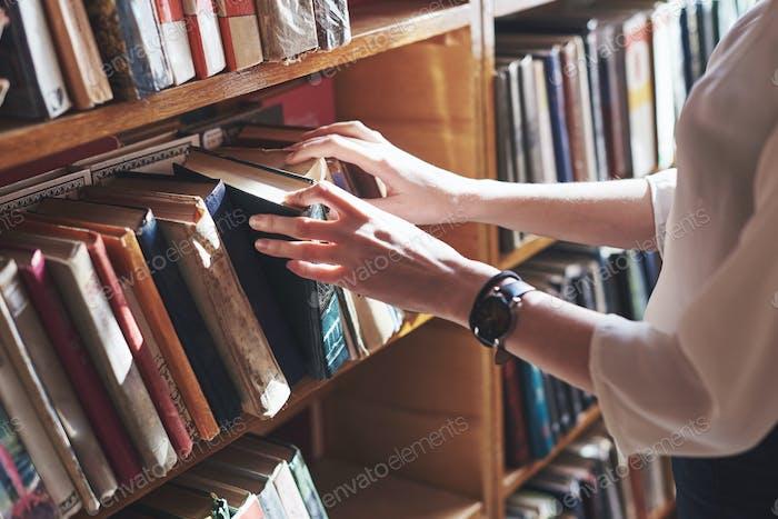 Ein junges Mädchen Student auf der Suche nach Literatur in der Nähe der Bücherregale in der alten Bibliothek