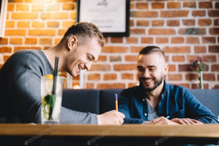 Two men sitting in a restaurant and laughing.