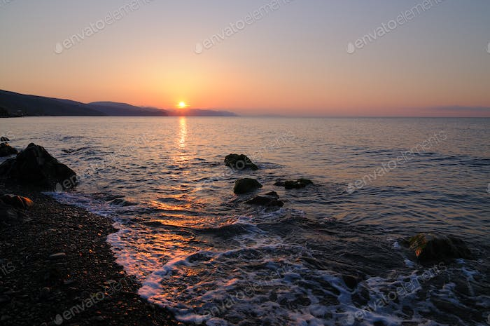 Sunset by the sea, beach strewn with stones