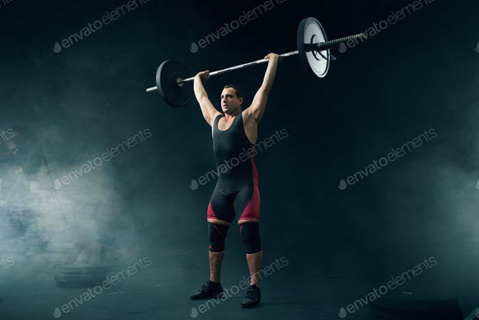 Strong weight lifter in sportswear takes a weight
