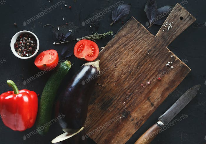 Wooden desk with vegetables on dark background