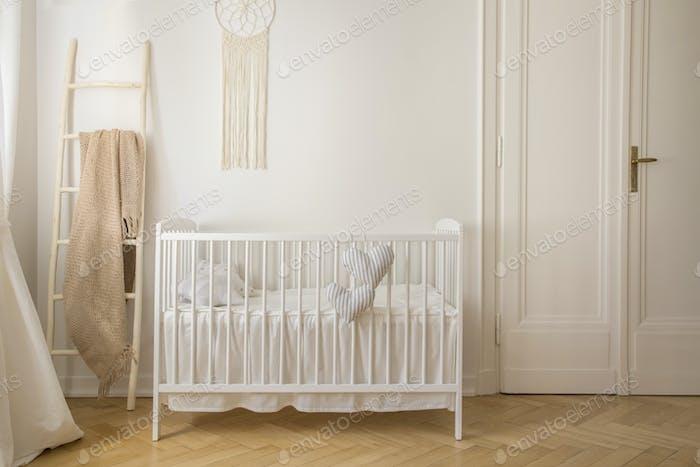 Skandinavisches Kinderzimmer mit weißer Holzkrippe und Makramee auf der W