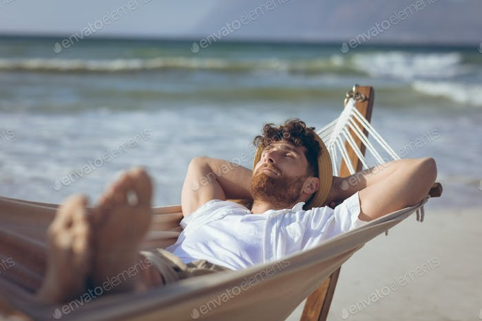 Front view of handsome young Caucasian man relaxing on hammock at beach on a sunny day
