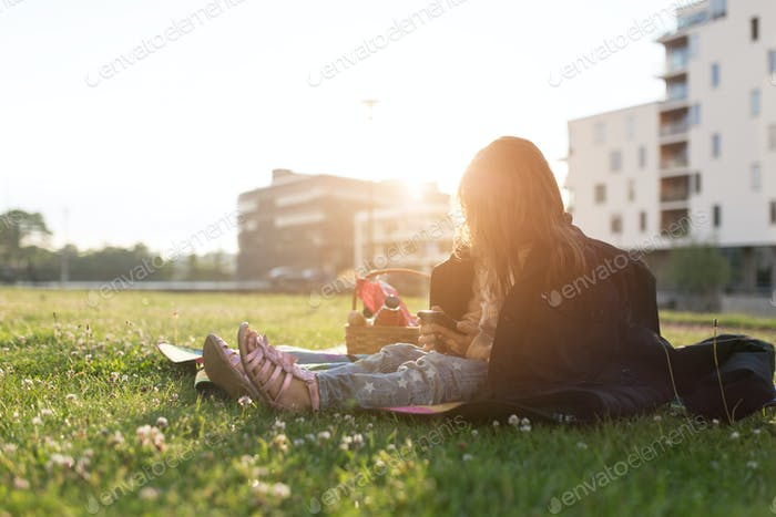 Girl (4-5) sitting on grass and using phone