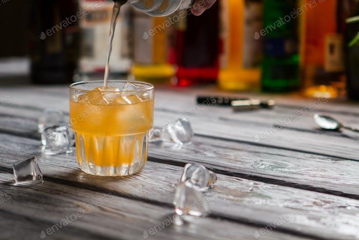 Orange liquid pours into glass