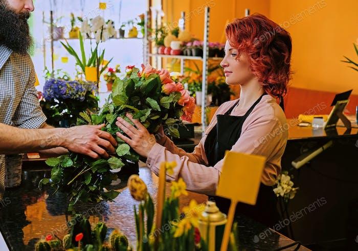Bärtige Männchen gibt Rosen Bouquet zu einem Rothaarigen Weibchen in einem Markt