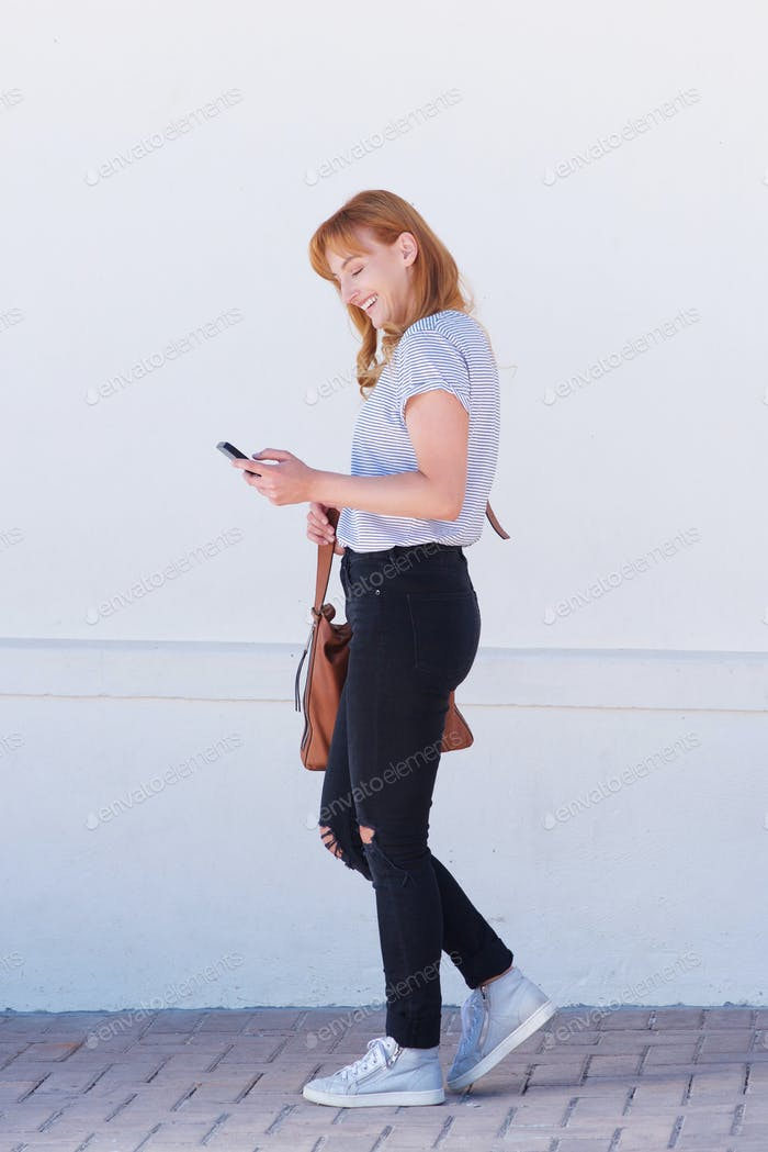 portrait of smiling woman walking with mobile phone