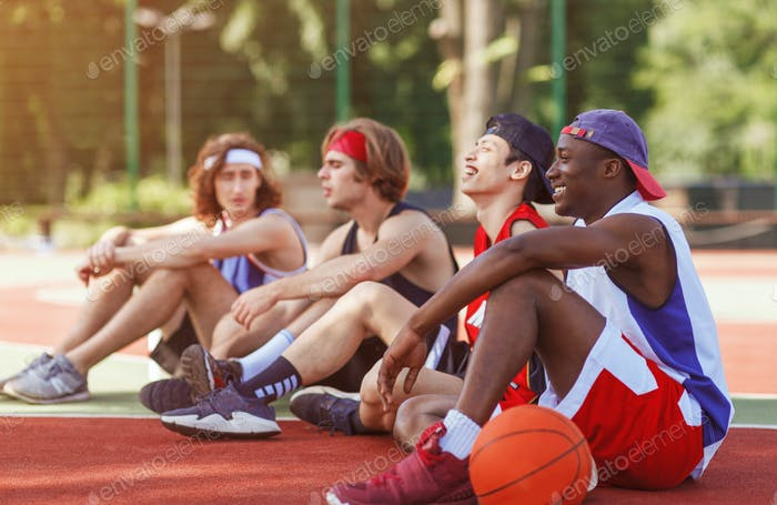 Team of professional basketballers communicating after tournament at outdoor arena, copy space