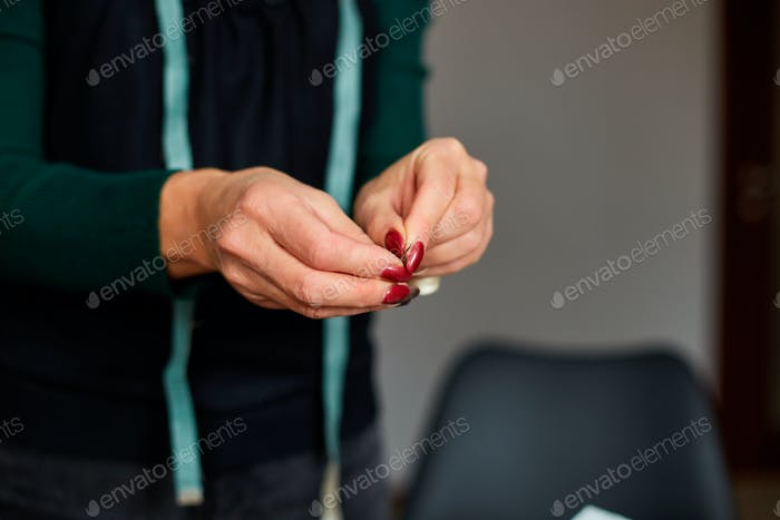 Step by step, woman dressmaker pulling thread into the needle