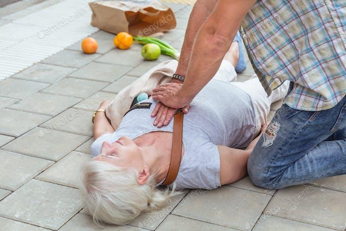 Mann führt eine Herzmassage auf einer Seniorin, die auf der Straße in Ohnmacht gefallen