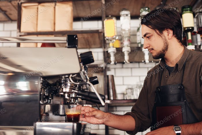 Barista masculino preparando espresso en la cafetería