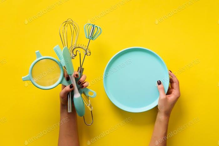 Frau Hand hält Küchenutensilien auf gelbem Hintergrund. Backwerkzeuge - Teller, Pinsel, Schneebesen