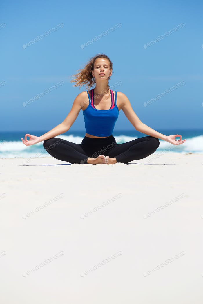 Woman sitting in yoga position at the beach