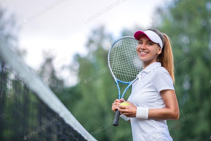 Glückliche Frau mit einem Tennisschläger