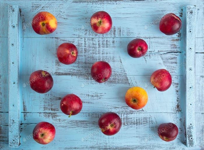 rote Äpfel, die weder gefärbt blau rustikalen Holztisch