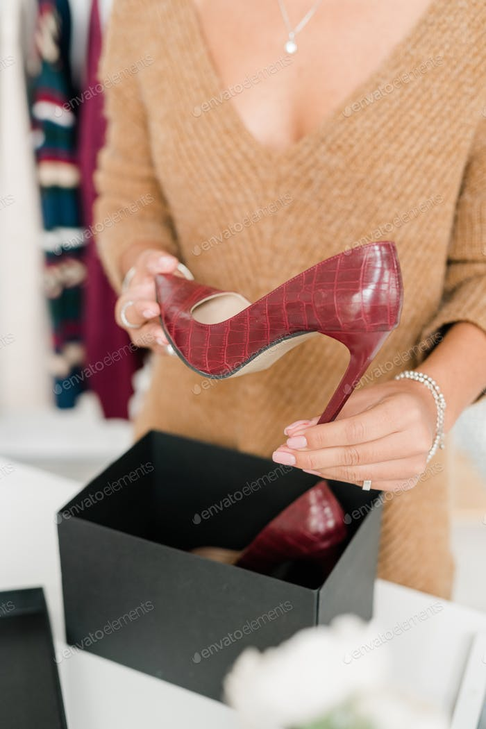 Young woman in casual beige pullover holding high-heeled maroon leather shoe