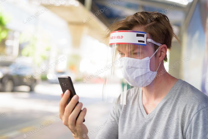 Young man with mask and face shield for protection from corona virus outbreak using phone at the bus
