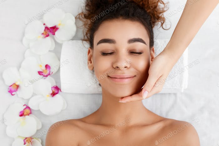 African-american woman getting face massage at beauty salon