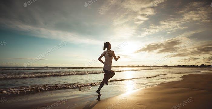 Woman running on sunset beach