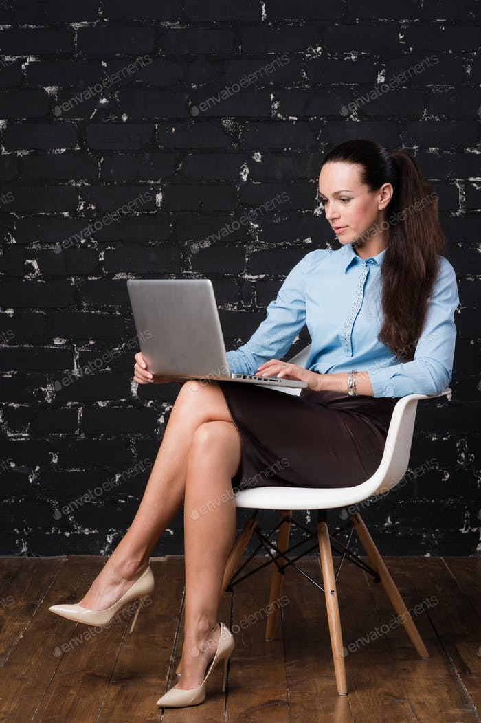 Porträt einer lächelnden Geschäftsfrau mit Laptop sitzen auf Loft-Raum