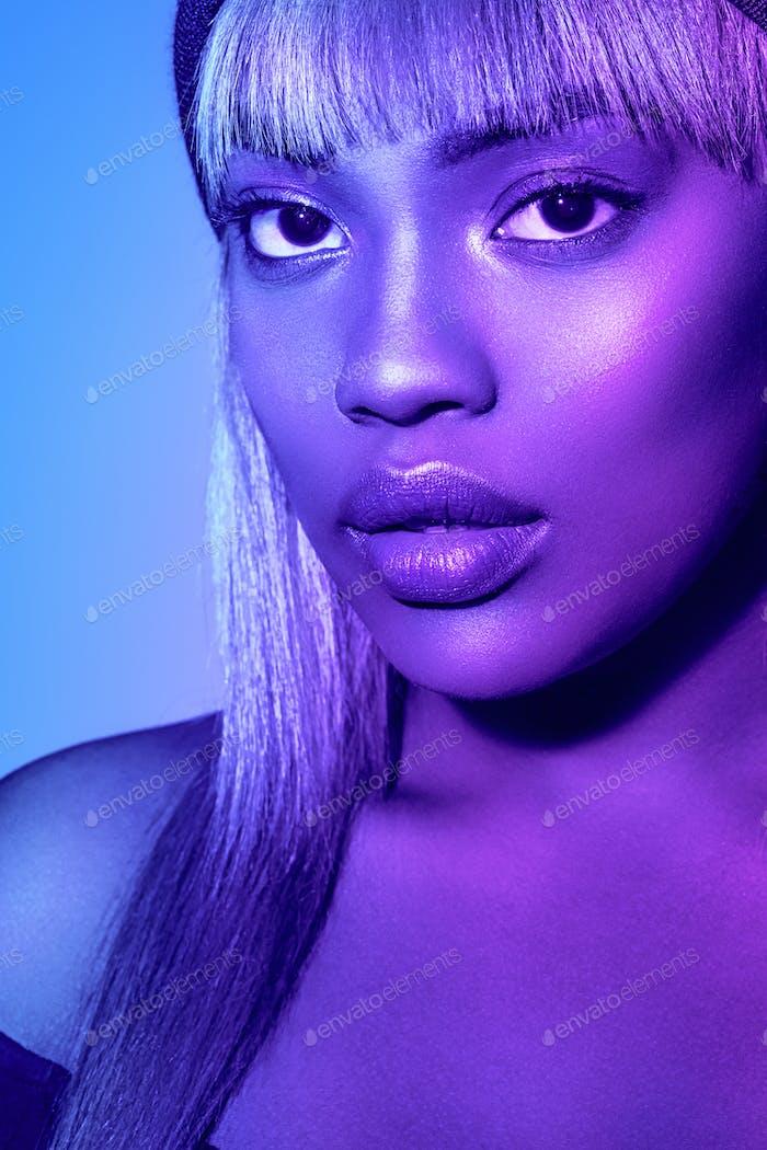 Neon color woman afro blue color. Studio shot.