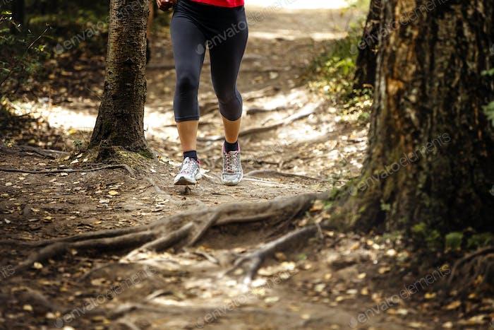 Frau läuft in Wald Trail