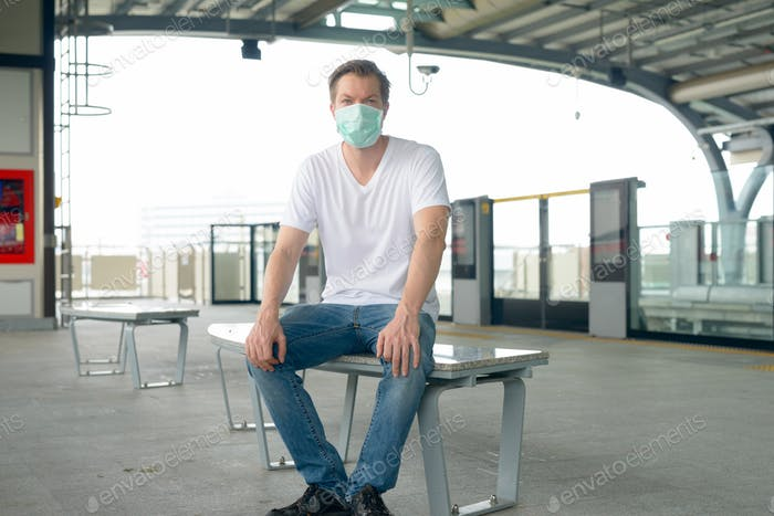 Young man with mask for protection from corona virus outbreak sitting at the train station