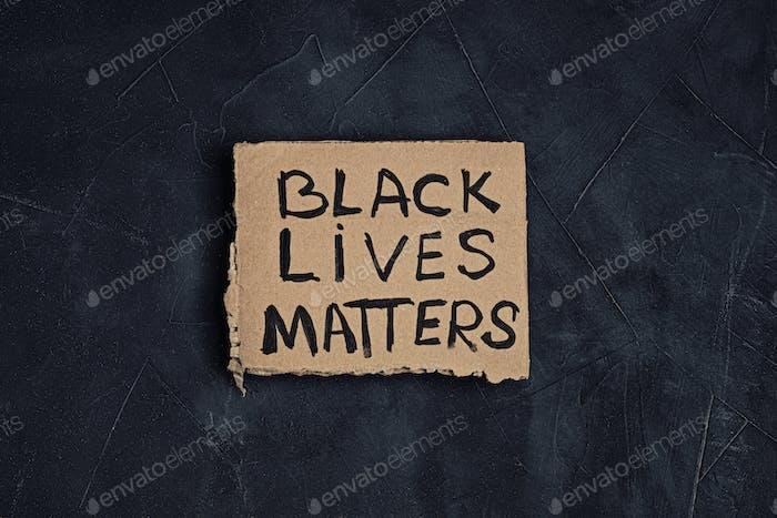 Black lives matter text on cardboard on dark background