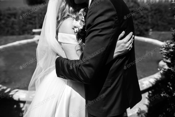 Stylish bride in silk dress and groom in suit kissing in sunny garden on wedding day
