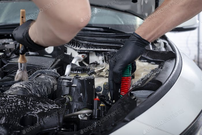 Car detailing  maintenance cleaning engine with the foam and a brush