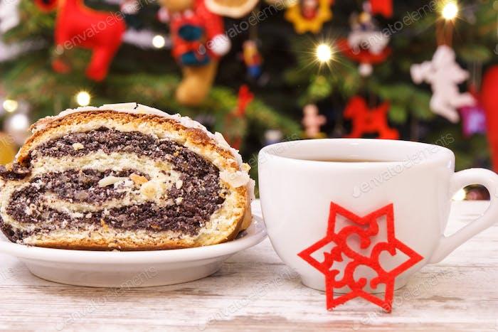 Polnischer Mohnkuchen, Kaffee oder Tee und Weihnachtsbaum mit Beleuchtung und Dekoration
