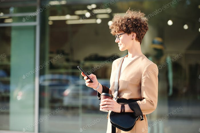 Curly brunette businesswoman with drink and handbag messaging in smartphone