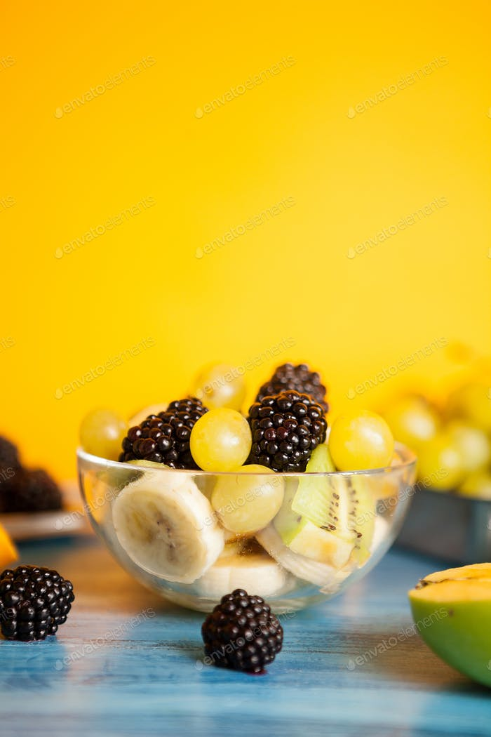 Diet fresh tasty mix of fruits in a bowl on a wooden table