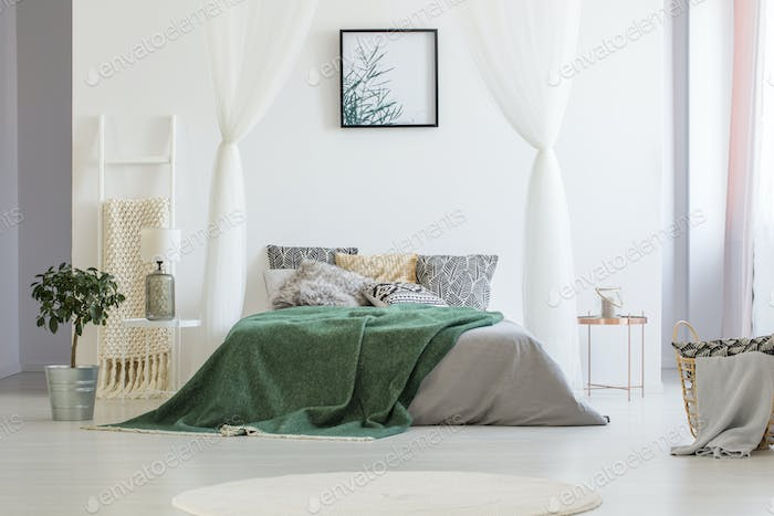 Green blanket thrown on double bed with many pillows and grey sh