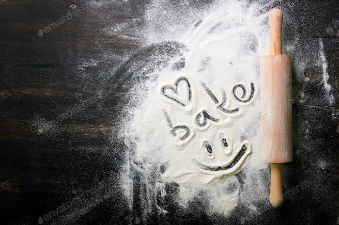 Baking background. Heart of flour, text Cook and rolling pin on dark table with copy space, top view