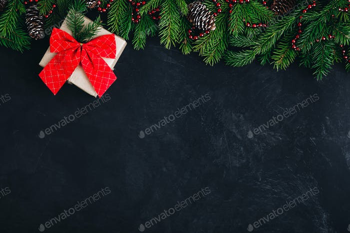 Christmas festive background with christmas tree branches, fir cones and gift box