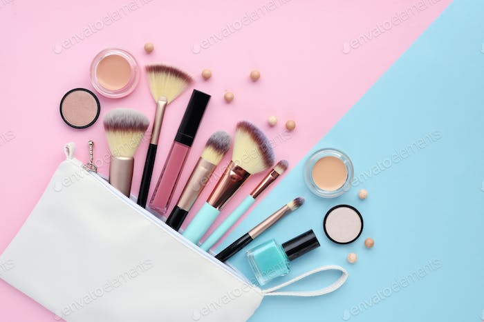 A white cosmetics bag with makeup products spilling out on to a