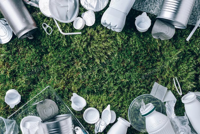 Reuse garbage, recycle, plastic free. Food plastic packaging, trash on green moss background after