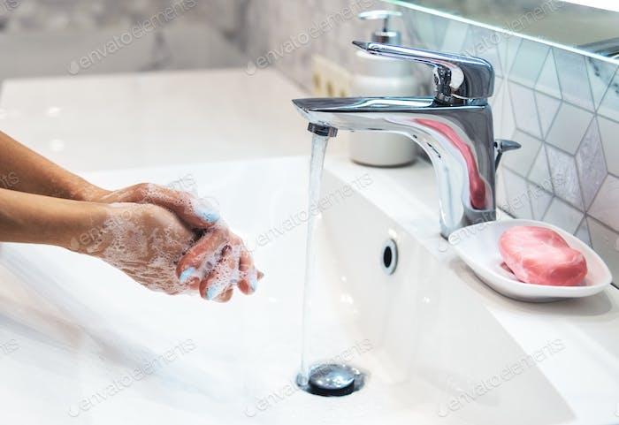 Woman is washing hands with soap. Coronavirus pandemic. Covid-19