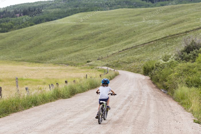 rear view of 5 year old boy biking on country road