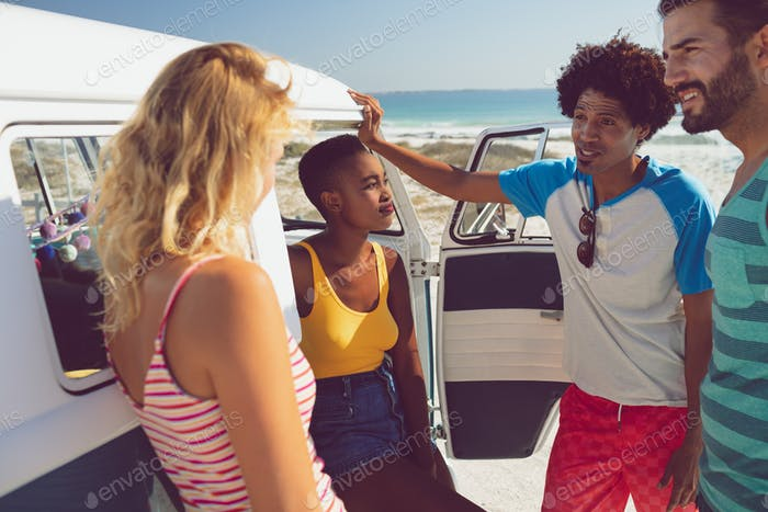 Young group of diverse friends talking with each other near camper van at beach in the sunshine